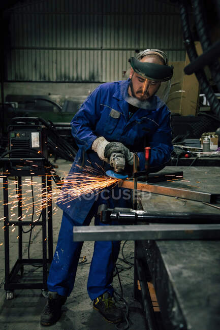 Full body of workman in protective mask and blue workwear grinding metal part with angle grinder at workbench in professional garage — Stock Photo