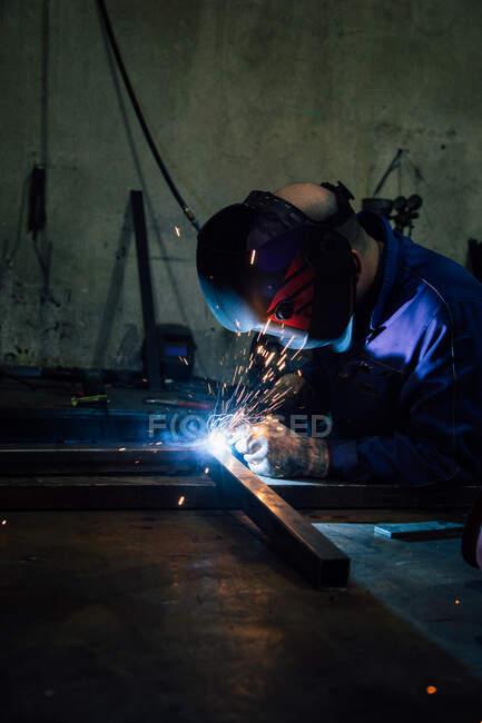 Безликий работник в перчатках и унифицированных сварных металлических деталях на столе рядом со строениями на заводе — стоковое фото