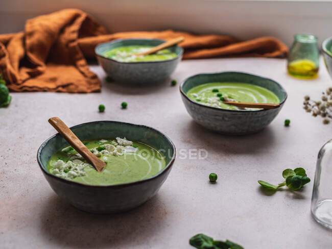 From above of delicious pea cream soup in bowls served on table with napkin and vase with flowers — Stock Photo