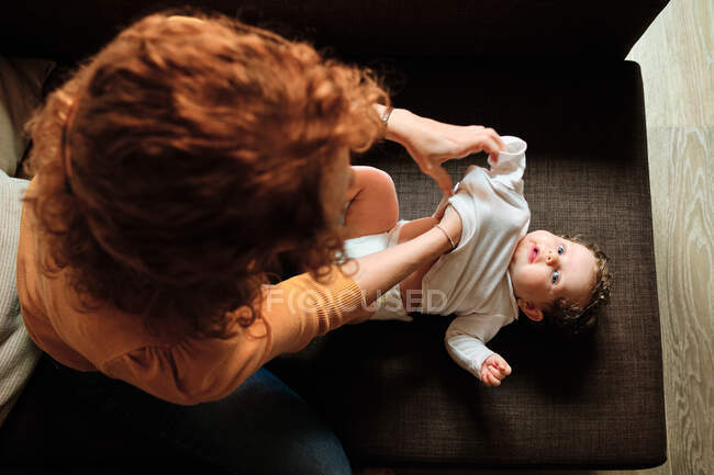 From above of unrecognizable single mother sitting on sofa and changing clothes of curious baby while spending time at home in daytime — Stock Photo