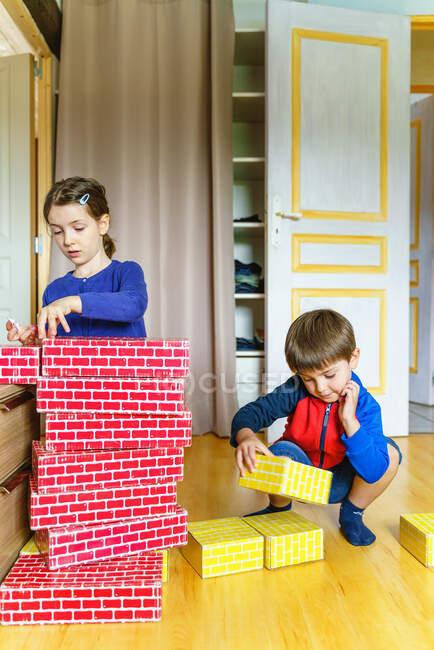 Vista laterale dei bambini che giocano a costruire con pezzi di cartone a casa — Foto stock
