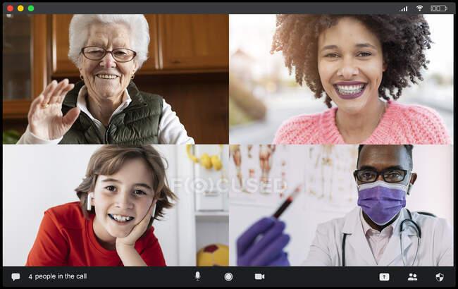 Médico masculino negro anónimo de la cosecha en uniforme médico y máscara que muestra el tubo de prueba con la muestra de sangre a las diversas mujeres y al niño envejecidos felices durante la consulta a distancia vía videollamada - foto de stock