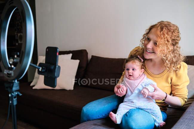Alegre madre soltera en ropa casual sentada con su hija pequeña y tomando fotos en el teléfono inteligente usando la lámpara de anillo led en el trípode en casa durante el día - foto de stock