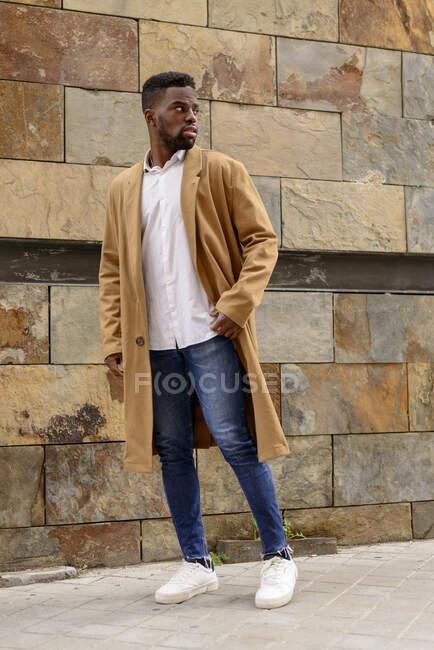 Cuerpo completo de hombre afroamericano con abrigo de moda de pie cerca de la pared de piedra del edificio en la ciudad y mirando hacia otro lado - foto de stock