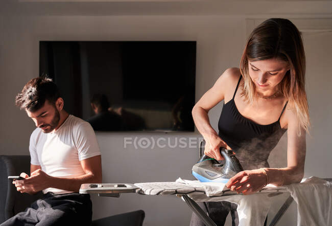 Young female ironing white shirt near concentrated ethnic husband using mobile phone on sunny day at home — Stock Photo