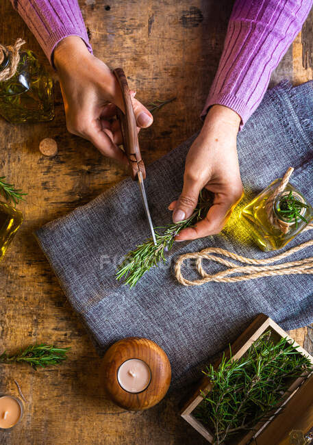 From above of crop lady cutting rosemary sprigs with scissors at table with fabric and rope near essential oil glass bottles and small chest — Stock Photo