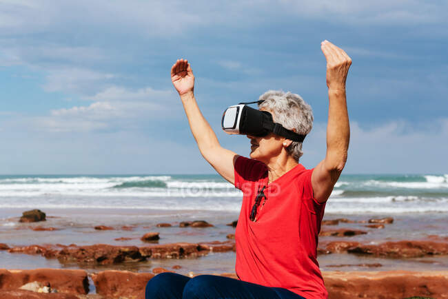 Anonymous elderly female traveler experiencing virtual reality in goggles on sea shore under cloudy sky — Stock Photo