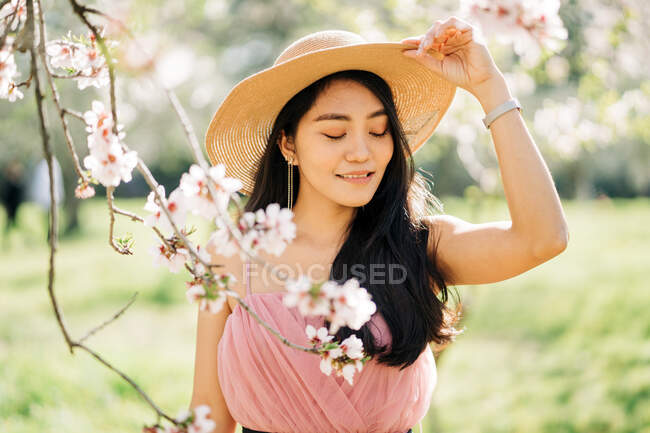 Peaceful happy ethnic female in straw hat and dress standing under blooming fragrant flowers on tree branches in orchard — Stock Photo
