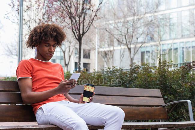 Confiado joven negro con pelo afro en ropa elegante usando teléfono inteligente y beber café para llevar mientras descansa en un banco de madera en el parque de la ciudad - foto de stock