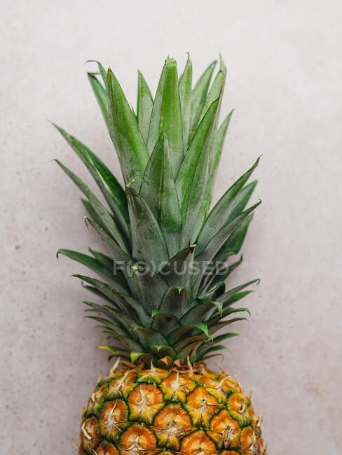 From above of ripe whole sweet pineapple placed on stone table in kitchen — Stock Photo