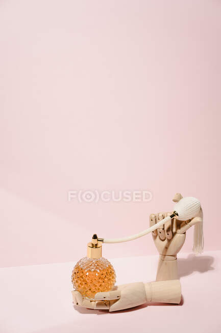 Stylish transparent bottle of perfume placed between wooden hands placed on pink background in light studio — Stock Photo