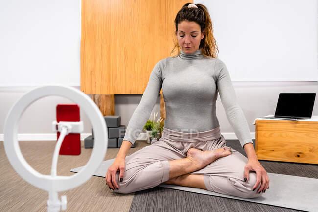 Тіло концентрованої молодої жінки в активаціях сидить в позі Лотоса з закритими очима і медитує під час сеансу йоги вдома біля смартфона, розміщеного на тринозі. — стокове фото