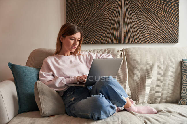 Full body of peaceful young female freelancer in casual clothes sitting on cozy sofa and working remotely on laptop — Stock Photo