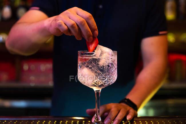 Невпізнаваний бармен прикрашає тонічний джин з полуницею в барі. — стокове фото