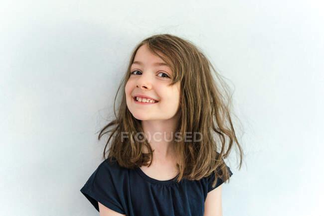 Gioioso ragazza carina con i capelli disordinati indossando camicia casual in piedi contro muro bianco e guardando la fotocamera con sorriso felice — Foto stock