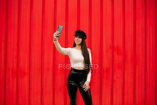 Alegre mujer emprendedora de moda de pie contra la pared roja en la ciudad y tomando uno mismo tiro en el teléfono inteligente - foto de stock