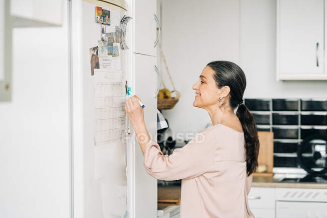 Side view of positive middle aged female making notes in calendar on fridge while having phone call in modern kitchen — Stock Photo