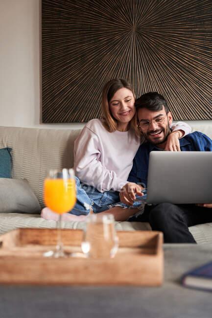 Весела молода багаторасова пара у повсякденному одязі посміхається, сидячи на дивані і спілкуючись за допомогою ноутбука. — стокове фото