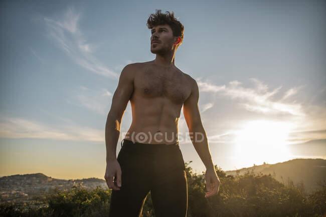 Hombre sin camisa con seis abdominales y barba mirando a las montañas bajo el cielo nublado por la noche - foto de stock