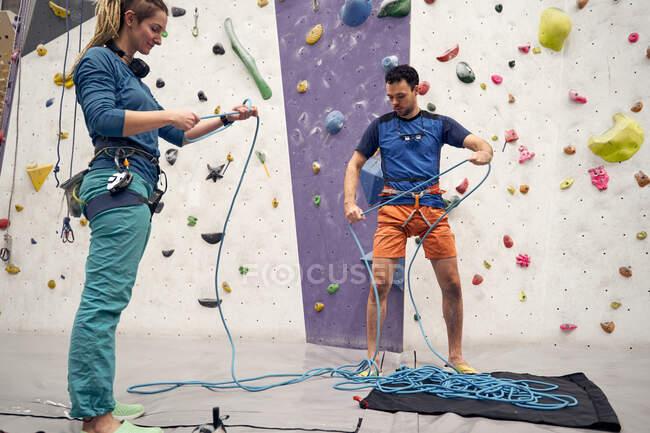 Низкий угол подготовки альпинистов и альпинисток к восхождению в современном боулдеринговом центре — стоковое фото