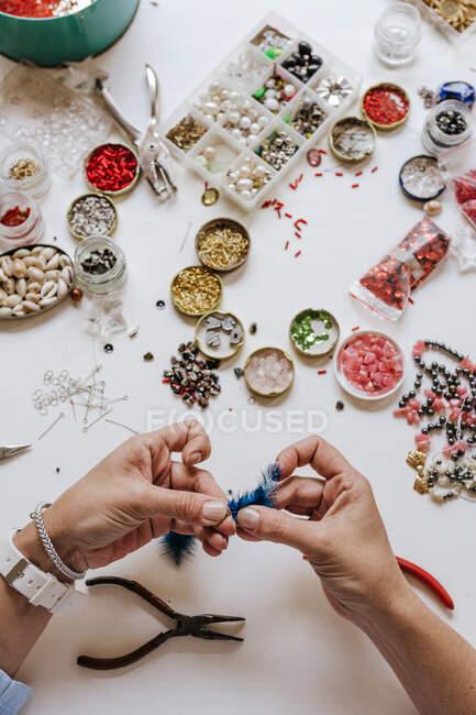 Alto ângulo de designer de culturas com pinça fazendo bijouterie decorativo sentado à mesa com diferentes cristais e lantejoulas — Fotografia de Stock