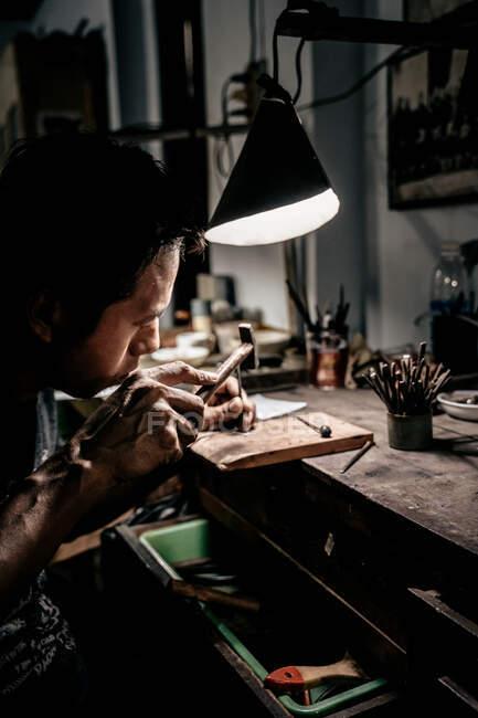 Seitenansicht eines ethnischen Handwerkers, der Metallstück aus der Nähe betrachtet und Metallstempel mit kleinem Hammer schlägt — Stockfoto