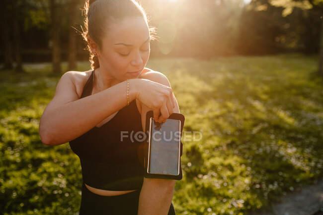 Обрезать молодую спортсменку в спортивной одежде с держателем сотового телефона на руке на лугу в задней освещении — стоковое фото