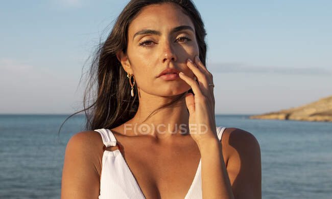 Young pretty female in swimwear looking at camera while standing on sandy shore against ocean under cloudy blue sky — Stock Photo
