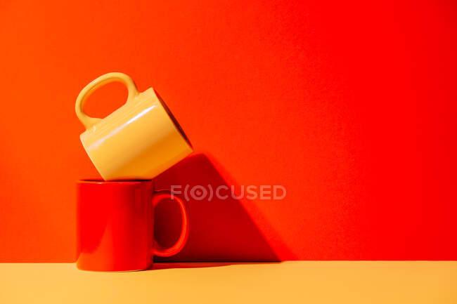 Tazas coloridas creativas sobre fondo amarillo y rojo en el estudio - foto de stock