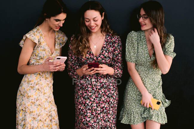 Contenu jeunes meilleures amies dans des vêtements à la mode avec des téléphones portables debout sur une passerelle urbaine contre un mur — Photo de stock
