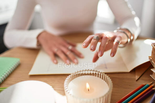 Cultivo irreconocible astrólogo buceo futuro en el escritorio con álbum de papel y vela encendida en casa - foto de stock