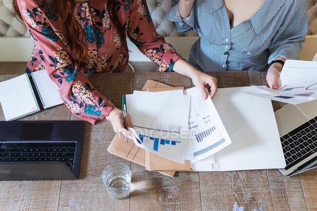 З - над врожаю жінки - співробітники, які збираються за столом за допомогою ноутбуків і аналізують діаграми, працюючи разом на сучасному робочому місці. — стокове фото
