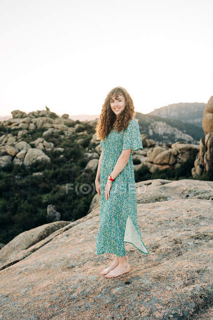 Full body attractive cheerful female in maxi sundress standing barefoot on rough rock in highlands and looking at camera — Stock Photo