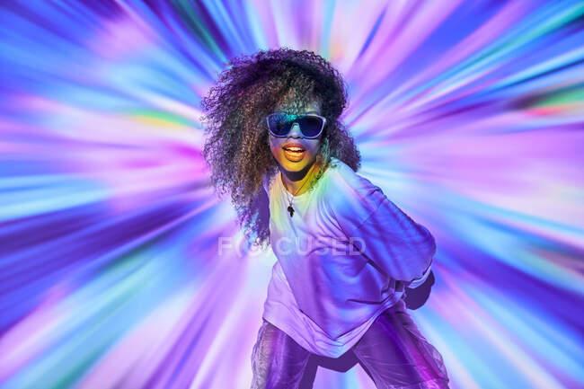 Elegante bailarina afroamericana confiada con pelo rizado en gafas de sol de pie en luces de neón en el estudio de baile - foto de stock