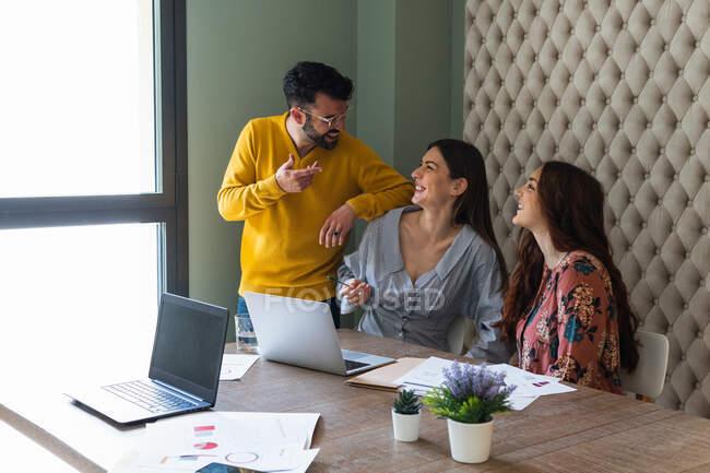 Grupo de colegas felizes rindo em roupas casuais que se reúnem na mesa com laptops e discutem detalhes de negócios enquanto trabalham juntos no escritório contemporâneo leve — Fotografia de Stock