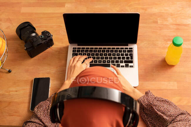 From above anonymous female in headscarf using modern netbook with black screen while sitting at desk — Stock Photo