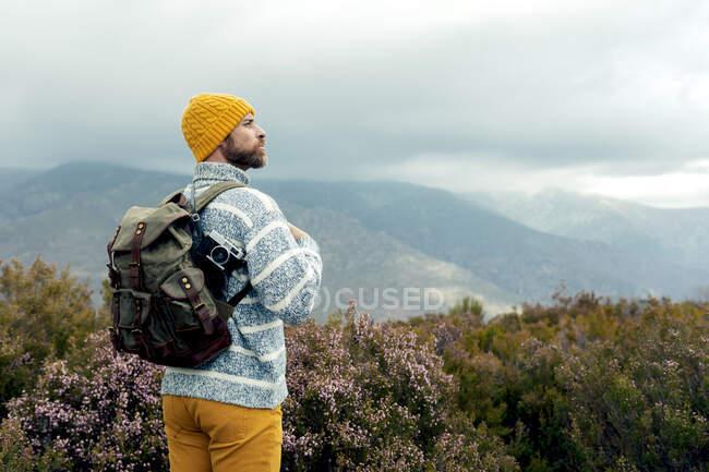 Vista posteriore di riflessivo camper maschile con cappello caldo in piedi con zaino in altopiani ammirando e godendo di panorami pittoreschi — Foto stock