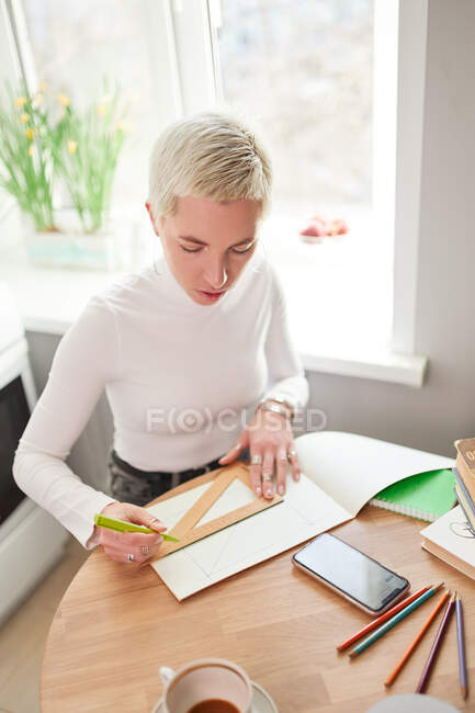 From above female astrologist taking notes in notepad at desk with cup of coffee at home in sunlight — Stock Photo