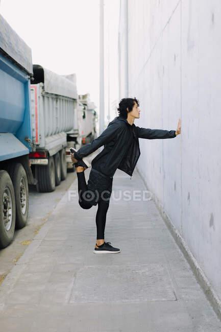 Vista laterale full body maschile in total black abbigliamento sportivo appoggiato a mano sul muro mentre si estende nel quartiere industriale della città — Foto stock