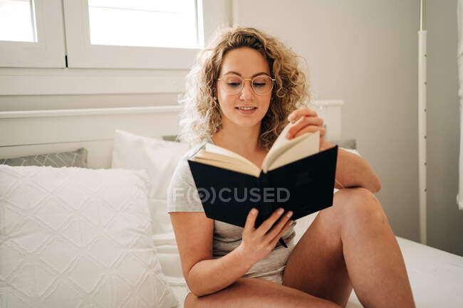 Positive young female with curly blond hair in panties and eyeglasses smiling while sitting on cozy bed and reading interesting book — Stock Photo