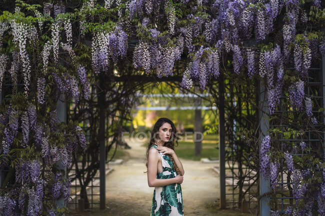 Side view attractive calm female in stylish sundress standing in verdant garden near blooming wistaria flowers while touching shoulder and looking at camera — Stock Photo