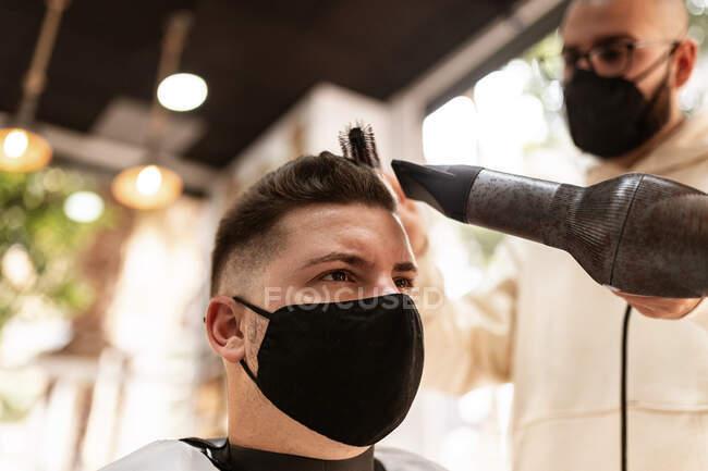 Знизу стиліст у текстильній масці з сушаркою для волосся проти чоловіка в плащі у кріслі в перукарні. — стокове фото