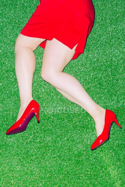 Visão superior da cultura fêmea anônima em sapatos vermelhos patente deitado em chão gramado — Fotografia de Stock