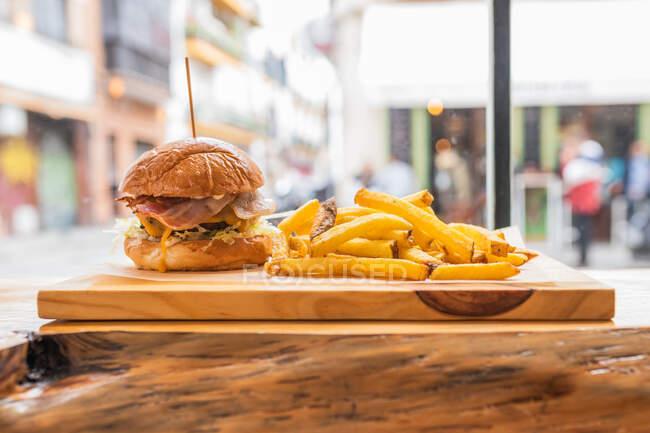 Deliciosa hamburguesa fresca y papas fritas crujientes servidas en tablero de madera en un moderno restaurante de comida rápida - foto de stock