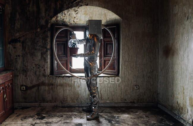 Vista lateral irreconocible persona con traje de plata con aparato de respiración y manguera adjunta a la planta en maceta de pie en la habitación abandonada en mal estado - foto de stock