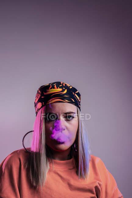 Cool hembra en traje de calle fumar cigarrillo electrónico y exhalación de humo a través de la nariz sobre fondo púrpura en el estudio con iluminación de neón rosa - foto de stock