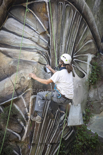 Back view full body of painter with spray paint making graffiti hanging on rope on steep rocky slope — Stock Photo