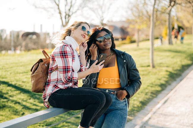 Stylish multiracial female friends listening to music in earphones together while enjoying weekend in park on sunny day — Stock Photo