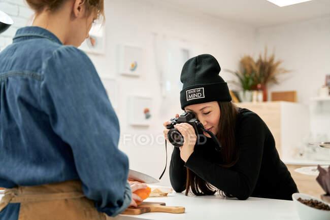 Кадрирование женщины со свежим сквошем на разделочной доске против этнической подруги делает фото на цифровой фотокамере в доме кухня — стоковое фото
