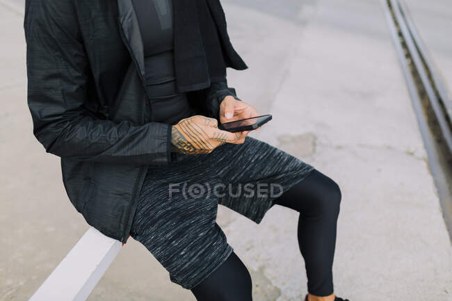 Crop man in black sportswear sitting on street fence and browsing smartphone against urban environment — Stock Photo